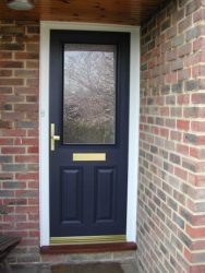 Blue composite entrance door with a white frame