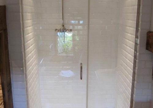 Glass shower door with a metal handle