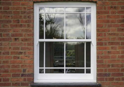White uPVC sliding sash window with white astragal bars