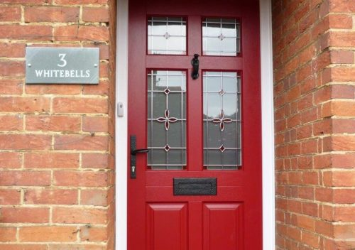 Red timber entrance door with a white frame
