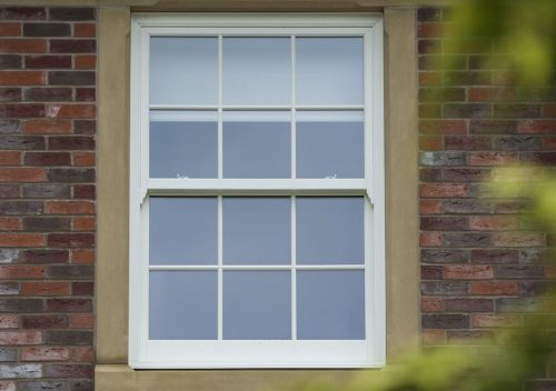 White pvc sliding sash window with a concrete frame
