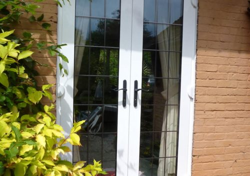 White aluminium french doors with leaded glass