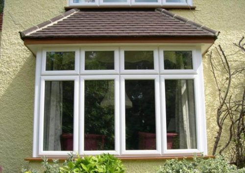 White uPVC casement bay windows on a yellow building